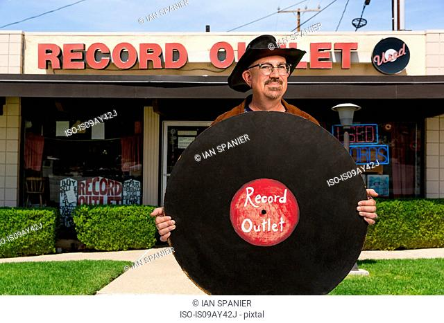 Portrait of mature man outside record shop, holding large imitation record