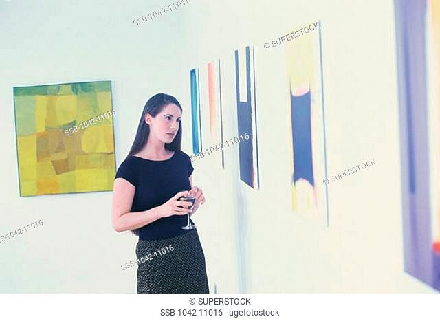 Young woman holding a glass looking at paintings on a wall