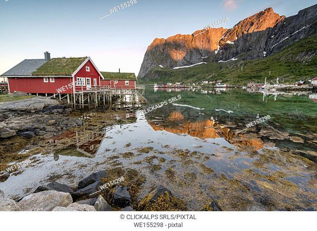 Fishing village and peaks reflected in water under midnight sun Reine Nordland county Lofoten Islands Northern Norway Europe