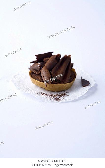 A miniature chocolate tartlet against a white background