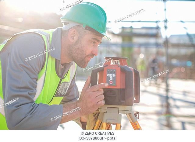 Construction worker using surveying equipment