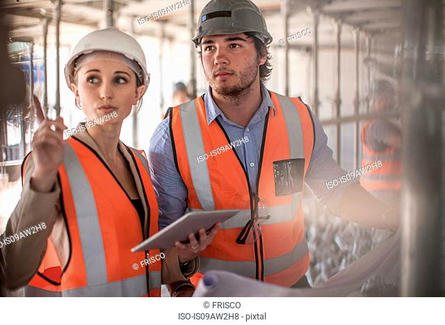 Female and male builders using digital tablet on construction site