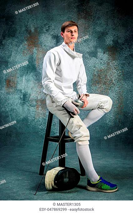 The man wearing fencing suit posing with sword against gray studio background