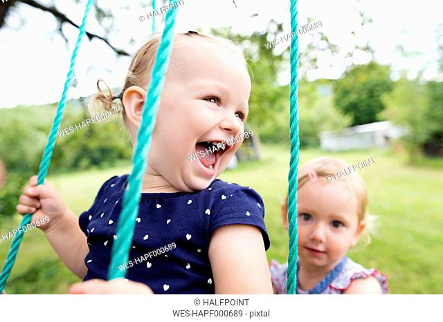 Laughing little girl on a swing with sister in the background