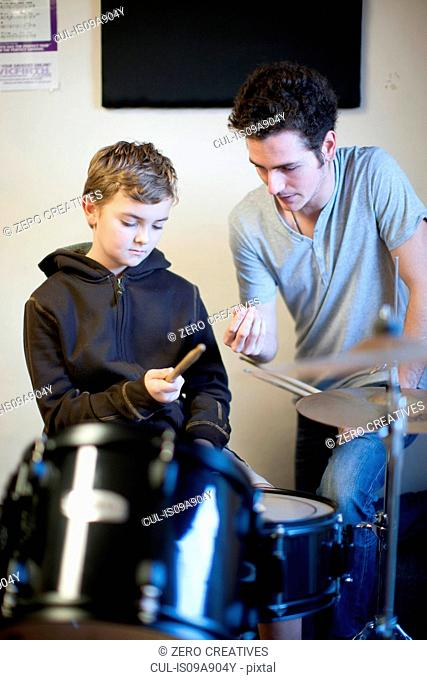 Young male teaching boy how to hold drumsticks