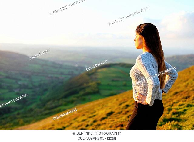 Rear view of young woman looking out over Glyn Collwn valley, Brecon Beacons, Powys, Wales