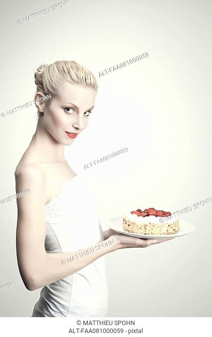 Young woman holding strawberry cake, portrait