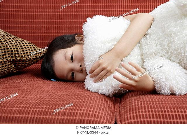 Girl lying in sofa with doll