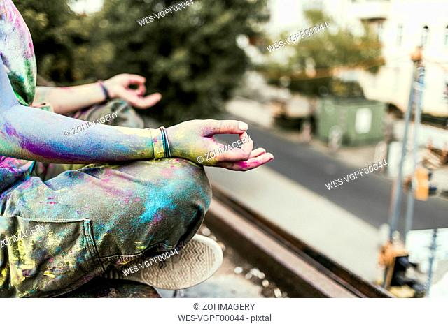 Girl with Holi colours on her clothes sitting on bridge, meditationg, Germany