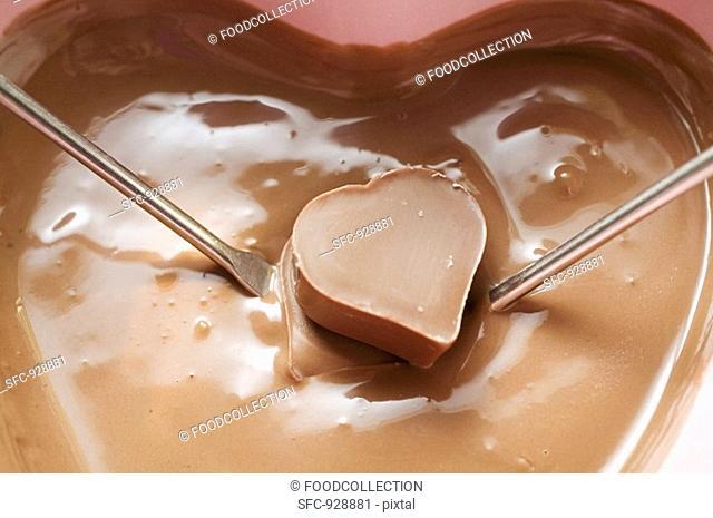 Chocolate fondue with heart-shaped chocolate on 2 fondue forks