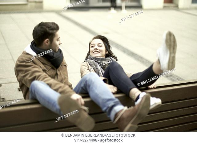 young unconventional teenage couple sitting on bench the wrong way round in city, hanging out together, legs up, upside down, in Cottbus, Brandenburg, Germany