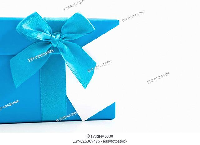 Decorative blue Christmas gift tied with a ribbon and bow with a blank white gift tag for your seasonal greeting or message