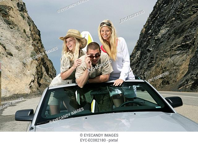 Portrait of young man with identical twins standing in convertible