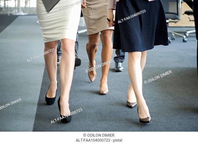 Businesswomen walking in office, low section