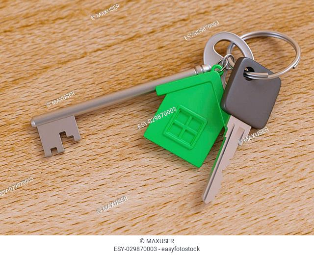 Green house keychain and house keys on wooden table close-up