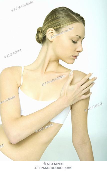 Young woman touching shoulder