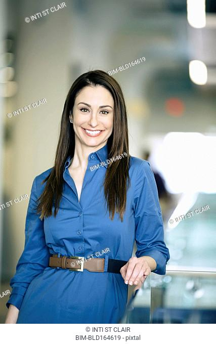 Caucasian businesswoman smiling in office