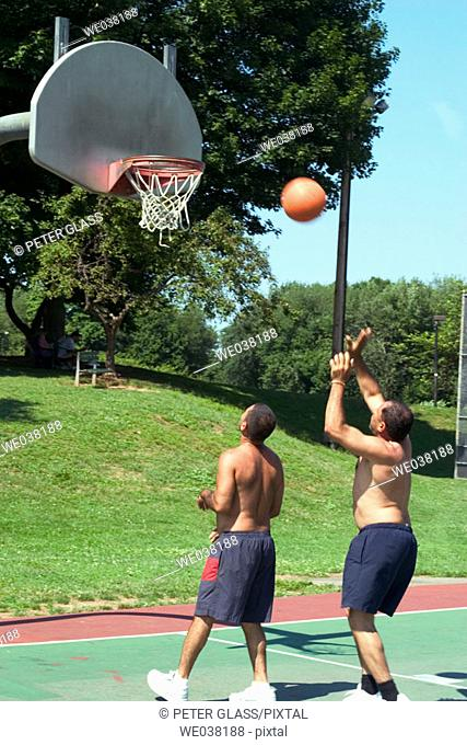 Two middle-age Spanish men playing basketball at a local park