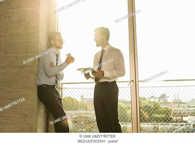 Two young businessmen talking at the window in office