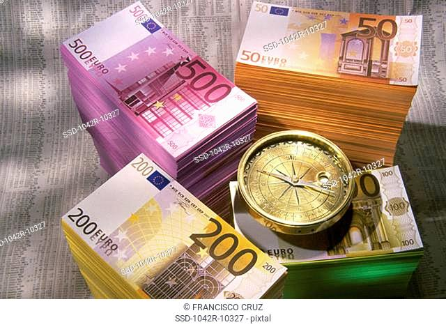 Stack of Euros and a compass