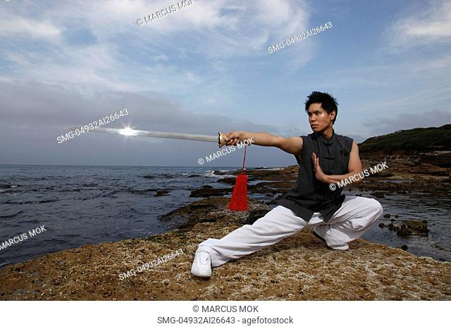 Chinese man doing martial arts and pointing sword