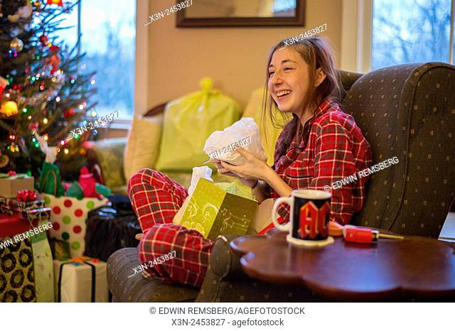 Young woman opening Christmas present wearing plaid pajamas in Fallston, Maryland, USA