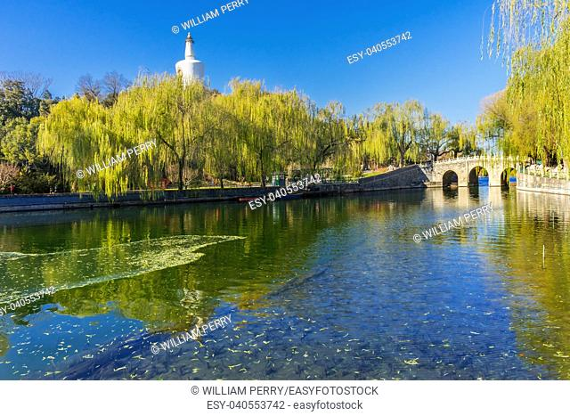 Willows Bridge Buddhist White Stupa Dagoba Gate Jade Flower Island Beijing China Beihai public park created 1000 AD. Stupa built in 1600s.
