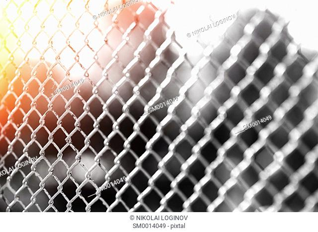 Horizontal prison fence with light leak bokeh background
