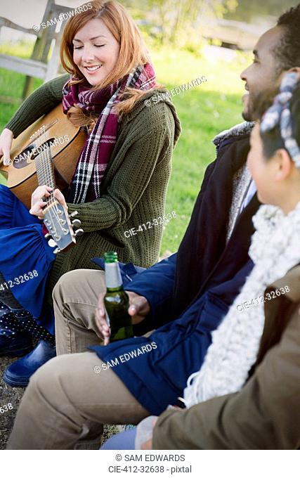 Woman playing guitar with friends drinking beer