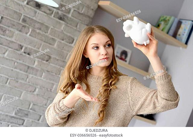 Young blonde woman holding piggy bank upside down