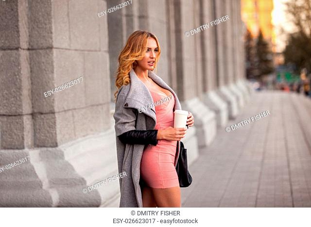 A pretty woman with a coffee to go against urban scene