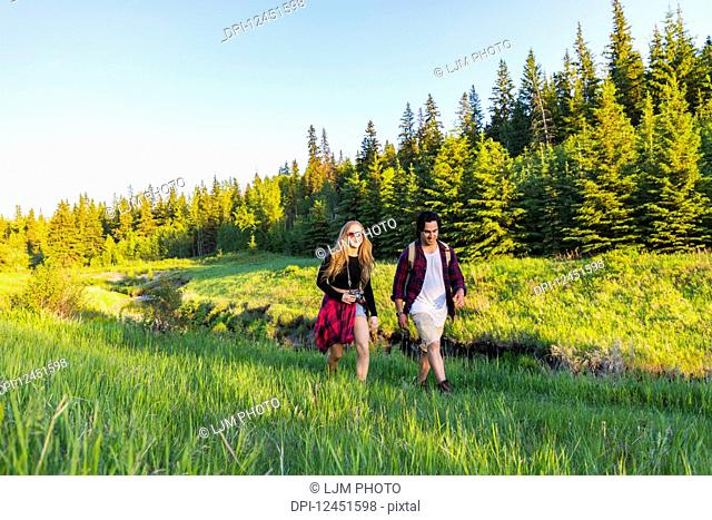Young couple walking together on a hike in a city park in autumn; Edmonton, Alberta, Canada