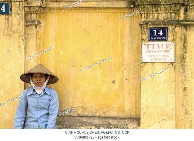 Woman resting on a wall, Hanoi, Vietnam