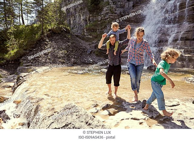 Two generation family having fun by waterfall, Ehrwald, Tyrol, Austria