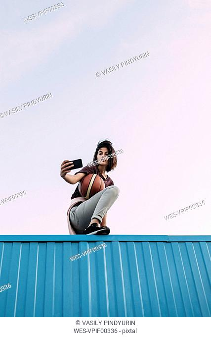 Young woman with basketball taking a selfie on container