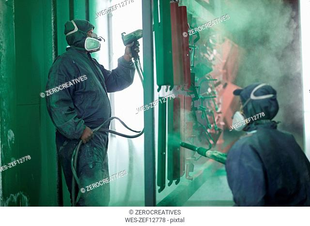 Painters spraying steel components in spray booth of a factory