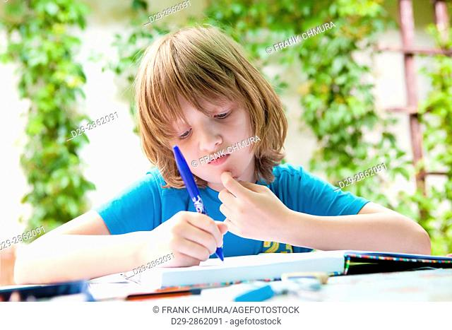 Boy with Blond Hair Doing Homework Outdoors