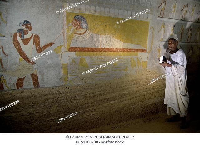 Grave guardian illuminating the mural of King Tanotamun on his deathbed in his grave, el-Kurru, Northern State, Nubia, Sudan