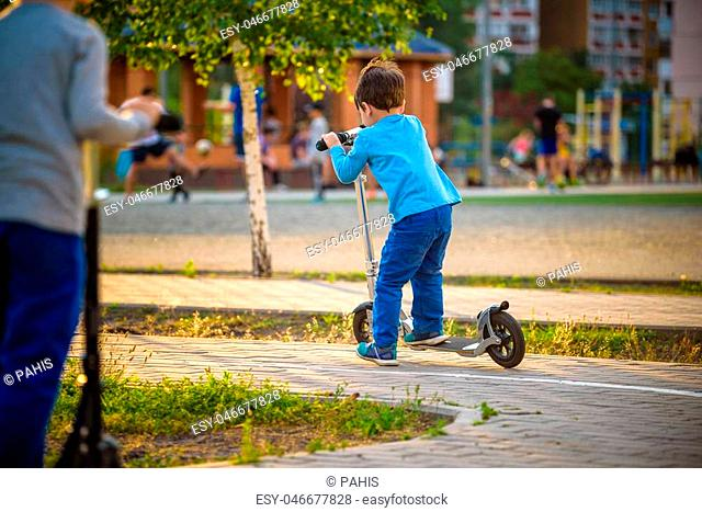 Two cute boys, compete in riding scooters, outdoor in the park, summertime. Kids are happy playing outdoors. Two brothers standing on their scooters