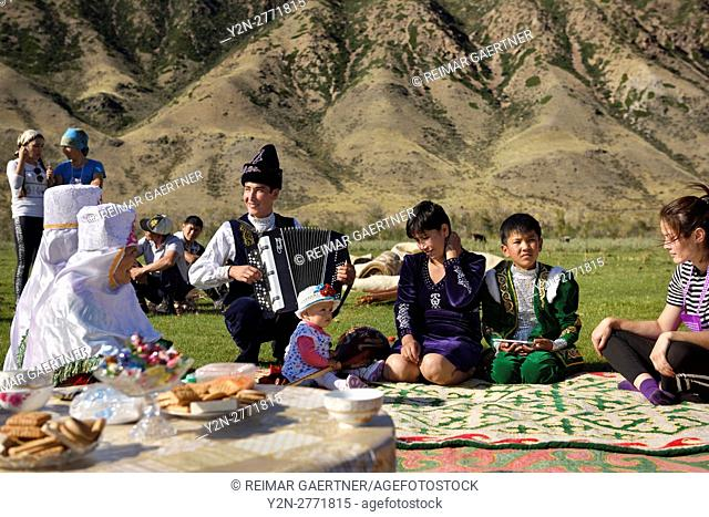 Saty townsfolk some in traditional clothes at a picnic by the Chilik river Kungey Alatau mountains Kazakhstan