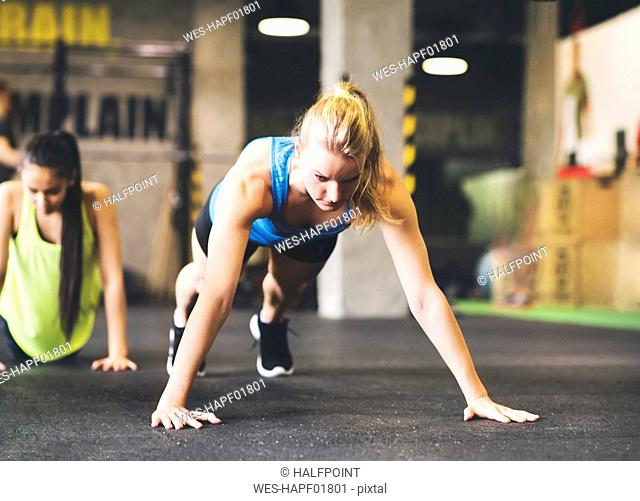 Young woman doing push-ups in gym