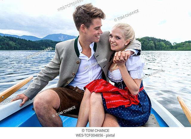 Germany, Bavaria, young couple sitting in a rowing boat on Staffelsee