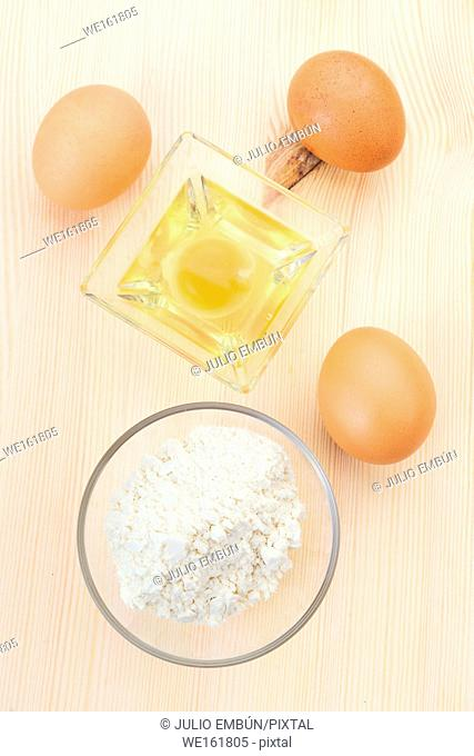 vertical take of flour eggs and kitchen utensils on natural wood