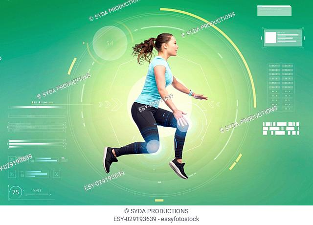 sport, fitness, technology, motion and people concept - happy smiling young woman jumping in air over white background