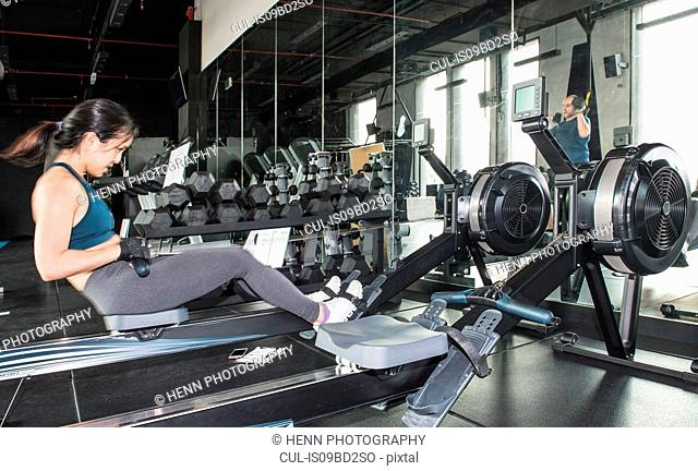 Woman working out in gym, using rowing machine