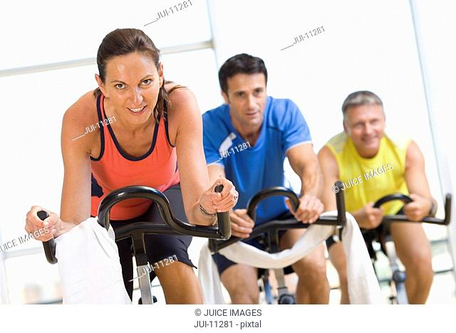 People on exercise bicycles in gym, smiling, portrait, low angle view