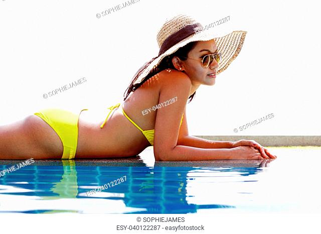 Young woman in a yellow swimsuit, a hat and sunglasses at a swimming pool on a sunny summer day