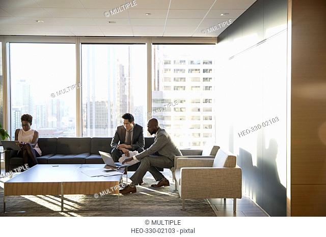 Business people working in highrise office lounge