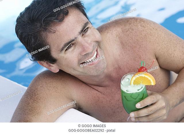 Man having tropical drink in pool