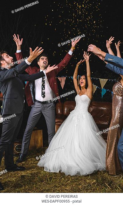Cheerful wedding couple and friends raising their arms while confetti falling over their heads on a night party outdoors